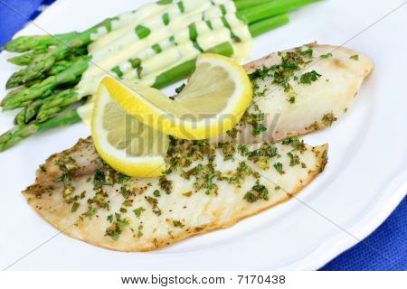 Fresh Baked Tilapia Fish Dinner With Asparagus And Hollandaise Sauce.