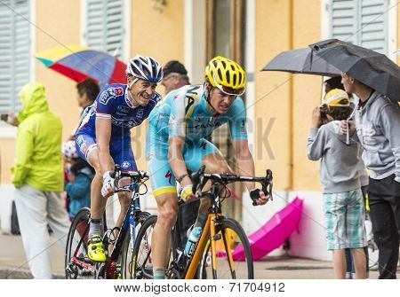 Two Cyclists Riding In The Rain