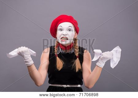 Portrait of female mime angry crumpling a paper isolated on grey