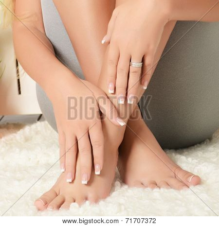Female hands and feet with manicure and pedicure