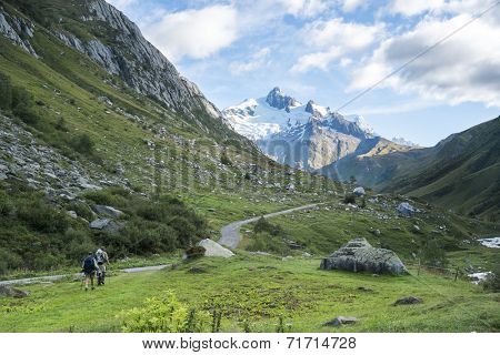 LES CHAPIEUX, FRANCE - AUGUST 27: Hikers walking with Glacier Needles in the background. The region is a stage at the Mont Blanc tour, which crosses three countries. August 27, 2014 in Les Chapieux.