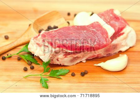 Raw Beef With Spices And Vegetables On The Cutting Board