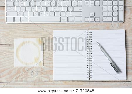 High angle shot of a white rustic desk with a modern keyboard, notebook and napkin with a coffee stain. Horizontal format.