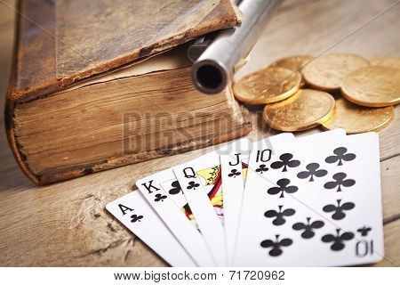 gambling and crime concept with gun, cards and golden coins