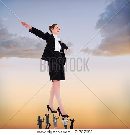 Business team supporting boss against beautiful orange and blue sky