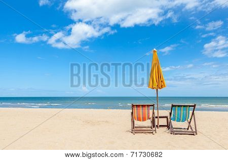 Colorful Two Beach Chairs With Sun Umbrella On Beautiful Beach With Cloudy Blue Sky.