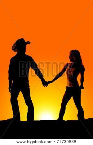 Silhouette couple hold hands western look back