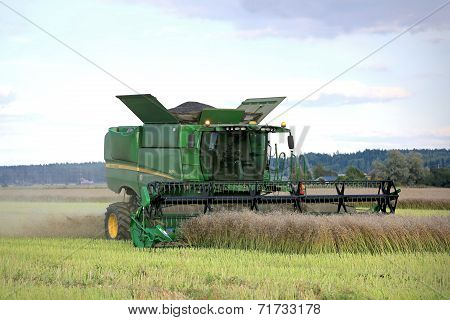 John Deere Combine On Rapeseed Field