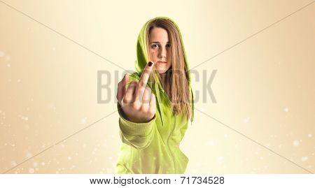 Girl Making Horn Gesture Over Ocher Background