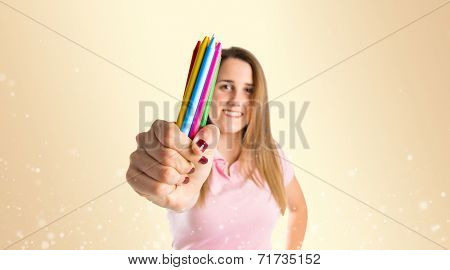 Blonde Girl Holding Crayons Over Ocher Background
