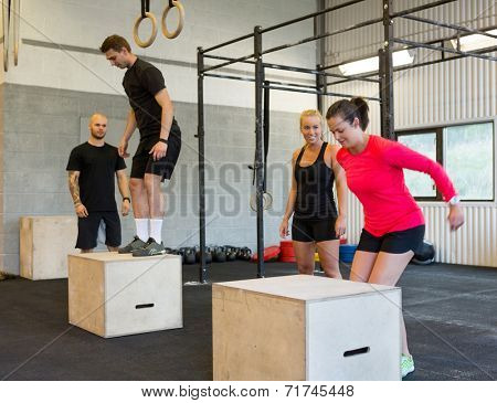 Group of male and female athletes box jumping