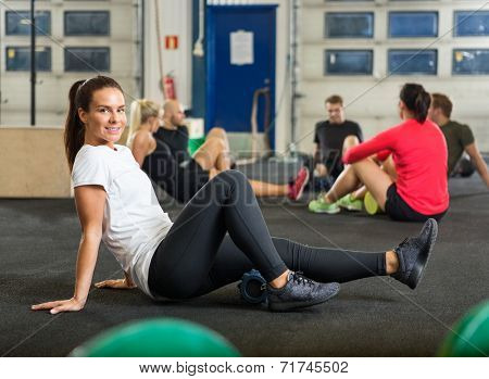 Full length portrait of young woman exercising in cross fitness box