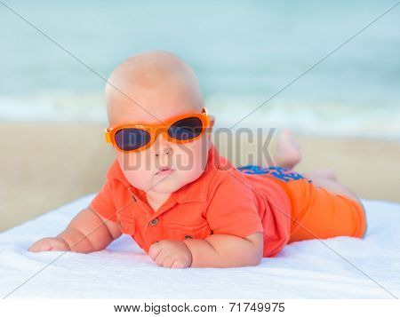 Cute baby laying on the sunbed at the beach