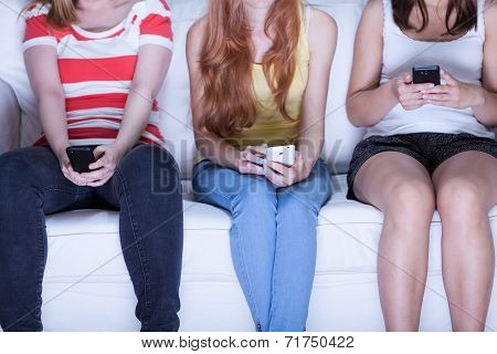 Friends Sitting On Sofa And Using Phones