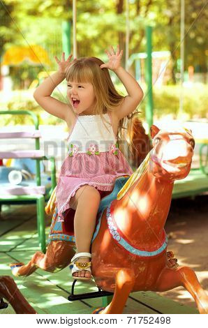 Happy beautiful girl on a merry-go-around