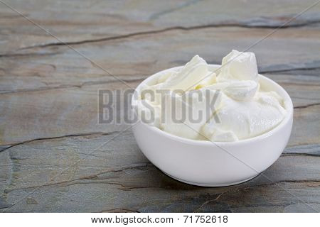 a small white bowl of Greek yogurt against slate rock background