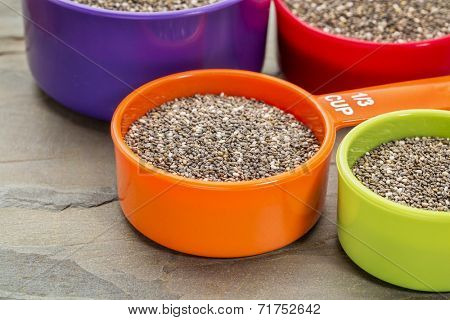 chia seeds in colorful measuring cups against slate rock background