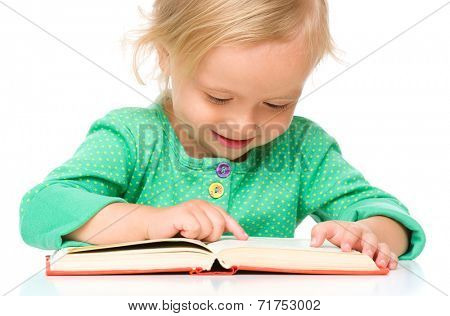 Little girl is reading her book, isolated over white
