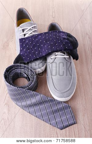 Top-Siders, pair of socks and tie on wooden background