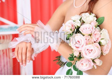 Beautiful bride in wedding  dress and gloves holding bouquet, close-up, on  home interior background