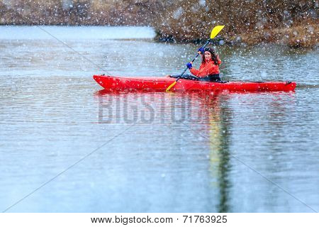 Kayaking on a lake under heavy snow