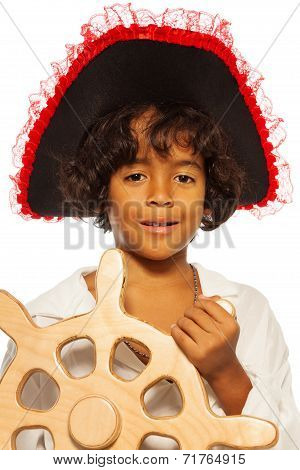 Portrait of a boy playing pirate steering helm