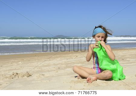 Summer vacation: Child inflating inflatable swim ring on the beach