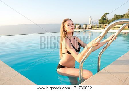 beautiful Blonde girl getting into a luxury pool