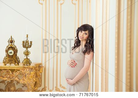 Fashionable Pregnant Mom In Golden Dress Hugging Tummy