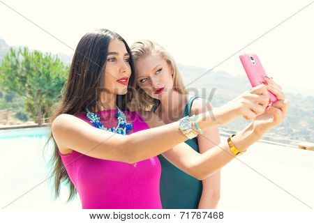 Beautiful girls taking a selfie with their cell phone