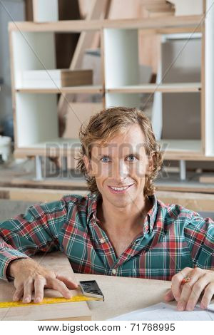 Portrait of confident carpenter smiling at workbench in workshop