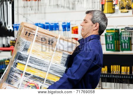 Side view of mature worker lifting heavy tool package in hardware shop