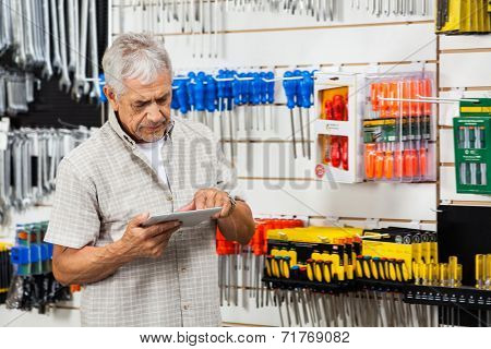 Senior male customer using tablet computer in hardware shop