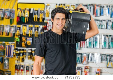 Portrait of smiling young man carrying toolbox on shoulder in hardware store
