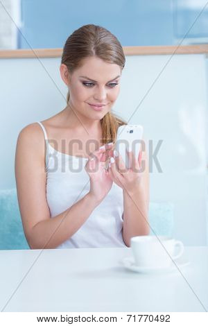 Smiling young woman sending an sms text messasge on her mobile phone as she sits at home enjoying a morning cup of coffee