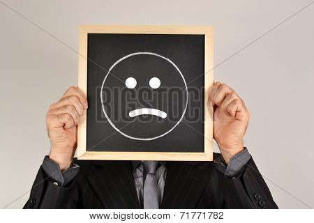 Businessman with sad face in blackboard on white background