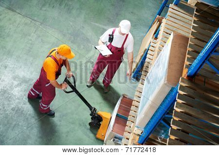 workers with fork pallet truck stacker in warehouse loading furniture panels