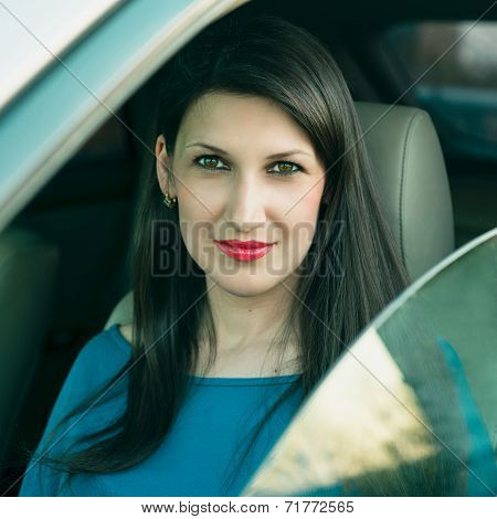 Beautiful young successful woman driving a car