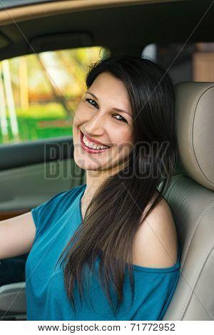 Beautiful young cheerful woman driving car