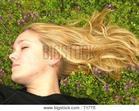 Blond Woman With Long Hair Napping In Grass