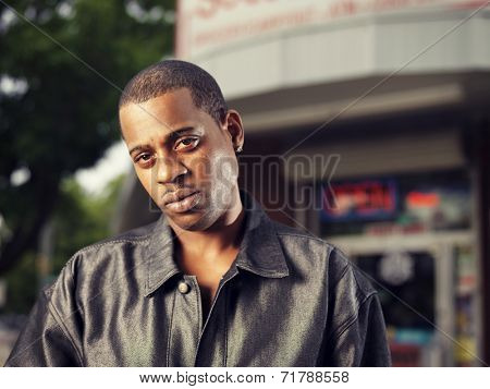 cool african man in front of corner store in ghetto
