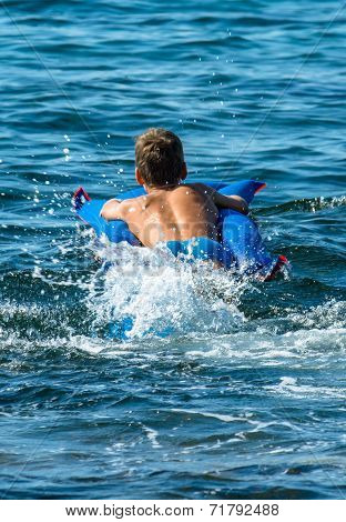 Young Boy on Airbed Splashing in the Sea