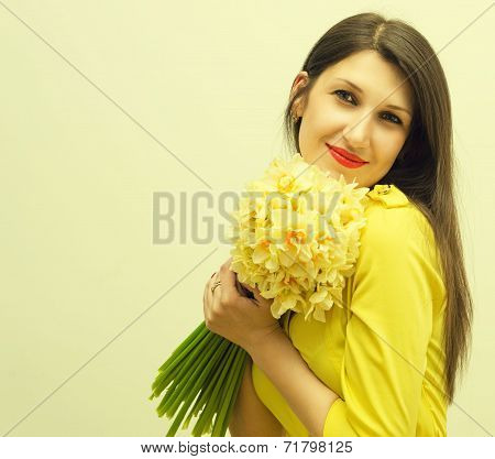 Young happy woman with a big bouquet of flowers in her hands