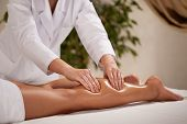 foto of calf  - Horizontal view of masseur massaging woman - JPG