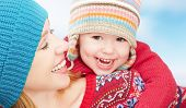 picture of mother baby nature  - happy family mother and baby little daughter playing in winter in warm sweaters and hats - JPG