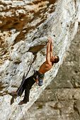 image of climbing wall  - Young man climbs on a rocky wall - JPG
