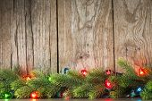 stock photo of fir  - Christmas tree branch with lights on grunge wood background - JPG
