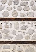 pic of gneiss  - Stone wall with two wooden beams closeup - JPG