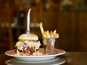 stock photo of jerks  - Photo of huge pulled pork sandwich with knife and bucket of garlic french fries on white plate with blurred background - JPG