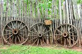 picture of log fence  - Antique wagon wheels lean up against a rustic log fence with trees in the background - JPG